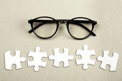 Incomplete puzzle on dark wooden table. Disconnected white jigsaw puzzle pices with eye glasses. Business and teamwork concept royalty free stock image