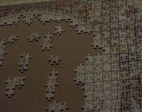 Incomplete Puzzle of many pieces in process and a cardboard as background. Incomplete white Puzzle in process over a cardboard as background stock photo