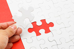 Incomplete puzzle with missing piece on human hand. In red colour stock images