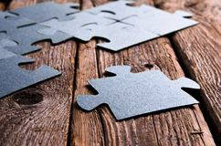 Incomplete puzzles lying on wooden rustic boards. Stock Photo
