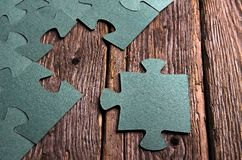 Incomplete puzzles lying on wooden rustic boards. Royalty Free Stock Photo