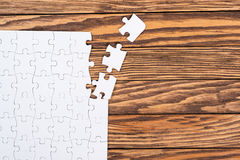 Incomplete white puzzles on wooden table. Stock Photo