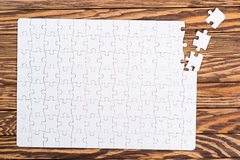 Incomplete white puzzles on wooden table. Stock Photography