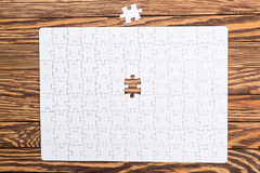 Incomplete white puzzles on wooden table. Stock Images