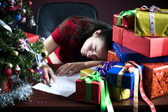Incomplete Wishlist. Girl sleeping on her office desk near Christmas presents and tree, with incomplete wishlist stock images