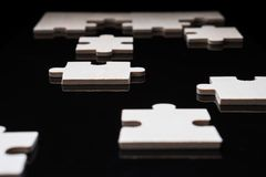 Incomplete wooden puzzles on brown wooden desk. Incomplete wooden puzzles on black background.The concept of logical thinking, business, conundrum. Business stock images