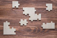Incomplete wooden puzzles on brown wooden desk, top view, flat lay. Frame with puzzle. The concept of logical thinking, business, conundrum. Business concept stock illustration