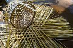 Incomplete work of basket weaving made of bamboo strips. Incomplete work of basket weaving made of bamboo strips lying on the floor with piles of bamboo strips stock photo