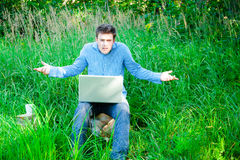 Young man outdoors with a cup and laptop Stock Images