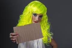 Inconformista, adolescente con la peluca amarilla fluorescente, llevando un cardbo Foto de archivo libre de regalías