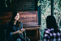 Inconformista adolescente de Asia en felicidad con el teléfono móvil y el amigo en café Imagenes de archivo