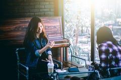 Inconformista adolescente en felicidad con el teléfono móvil y el amigo en café Fotos de archivo