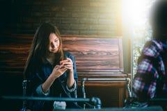 Inconformista adolescente en felicidad con el teléfono móvil y el amigo en café Imagen de archivo