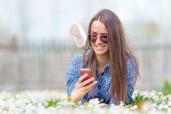 Inconformista adolescente joven al aire libre usando el teléfono móvil Imágenes de archivo libres de regalías