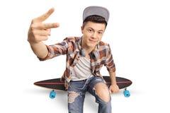 Inconformista adolescente que se sienta en un longboard y que hace una mano g de la paz Foto de archivo libre de regalías