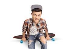 Inconformista adolescente que se sienta en un longboard y que mira la cámara Fotografía de archivo libre de regalías
