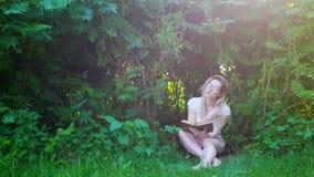 Inconformista atractivo de la mujer que sienta debajo de arbustos y que lee un libro en la puesta del sol almacen de video