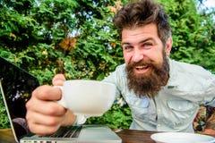 inconformista barbudo brutal en el descanso para tomar caf? Hombre feliz con la computadora port?til Negocio ?gil ?xito de asunto fotos de archivo