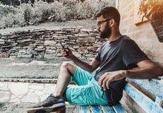 Inconformista barbudo en lentes en el banco al aire libre con el smartph fotografía de archivo