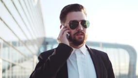 Inconformista barbudo joven elegante en un traje que contesta a la llamada de teléfono mientras que camina cerca del terminal de  almacen de metraje de vídeo