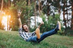 Inconformista barbudo joven sonriente que se sienta en la hierba Hombre barbudo con música que escucha de la tableta y de los aur Imagenes de archivo
