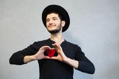 Inconformista barbudo joven vestido en negro, llevando a cabo el corazón rojo en manos Fondo del día de tarjetas del día de San V foto de archivo libre de regalías