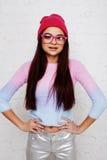 Inconformista bastante joven del adolescente en los vidrios rosados y la sonrisa feliz de presentación emocional del sombrero, co Imagen de archivo libre de regalías