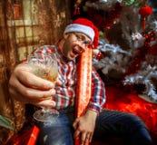 Inconformista borracho con el vidrio de champán debajo del árbol de navidad Fotos de archivo libres de regalías