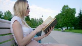 Inconformista caucásico de la mujer joven que lee un libro en el banco al aire libre almacen de metraje de vídeo