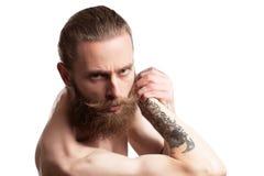 Inconformista con la barba larga en el fondo blanco Imagenes de archivo
