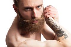 Inconformista con la barba larga en el fondo blanco Fotografía de archivo