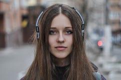 Inconformista de la muchacha en los auriculares que miran la cámara Foto de archivo libre de regalías