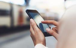 Inconformista del Blogger que usa en el teléfono móvil del artilugio de las manos, mensaje que manda un SMS en smartphone de la p imagen de archivo libre de regalías