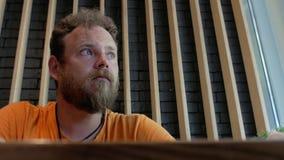 Inconformista del hombre con una barba que come la pizza en un café y que mastica a fondo 4K v?deo 4K almacen de video