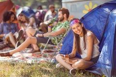 Inconformista despreocupado que sonríe en sitio para acampar Foto de archivo libre de regalías
