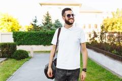 Inconformista elegante con una barba en una camiseta blanca, con un viaje b imágenes de archivo libres de regalías