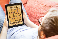 Inconformista en el sofá con la tableta del uso del sudoku Imagenes de archivo