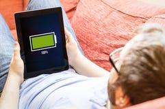 Inconformista en el sofá con la tableta llena de la batería Imagenes de archivo
