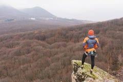 Inconformista - escalador en abajo una chaqueta y un soporte hecho punto y restos del casquillo en el top de una roca Imagen de archivo libre de regalías