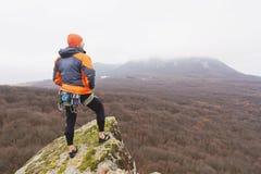 Inconformista - escalador en abajo una chaqueta y un soporte hecho punto y restos del casquillo en el top de una roca Fotos de archivo