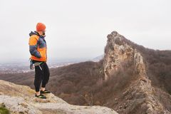 Inconformista - escalador en abajo una chaqueta y un soporte hecho punto y restos del casquillo en el top de una roca Foto de archivo libre de regalías