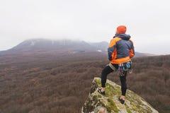 Inconformista - escalador en abajo una chaqueta y un soporte hecho punto y restos del casquillo en el top de una roca Imagen de archivo