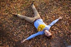 Inconformista feliz que miente en parque del otoño Imagenes de archivo