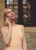 Inconformista femenino que tiene conversación telefónica de la célula que mira para arriba cuidadosamente Imagen de archivo