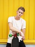 Inconformista hermoso con un monopatín Individuo joven serio que sostiene un longboard en un fondo amarillo Concepto del estilo d Imagenes de archivo