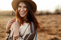 Inconformista hermoso de la mujer del boho, poncho sonriendo, el llevar sombrero y en la puesta del sol en montañas, emociones ve fotos de archivo libres de regalías
