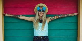 Inconformista hermoso de la mujer joven con un tatuaje en gafas de sol y un sombrero en un fondo coloreado brillante estilo de la foto de archivo
