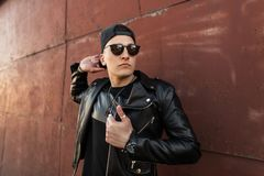Inconformista hermoso del hombre joven en una chaqueta negra de cuero elegante en un casquillo negro de moda en gafas de sol de m foto de archivo libre de regalías
