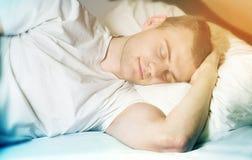 Inconformista hermoso del individuo, sin afeitar, durmiendo en su cama blanca Imagen de archivo libre de regalías