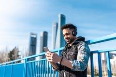 Inconformista hermoso Guy Listening Music en los auriculares y el teléfono móvil con imagen de archivo